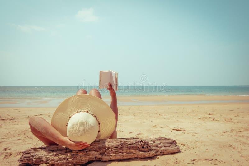 Молодая женщина в соломенной шляпе лежа для того чтобы загорать на тропическом пляже стоковое изображение rf