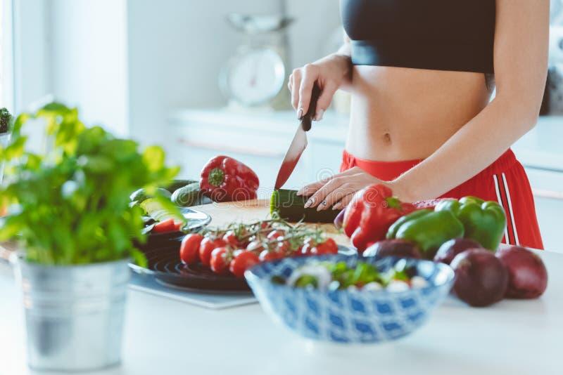 Молодая женщина в спорте одевает подготавливать салат в кухне стоковые фото