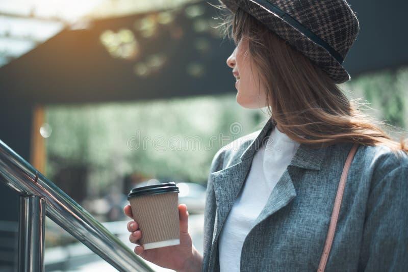 Молодая женщина в стильной шляпе с чашкой кофе стоковое изображение rf