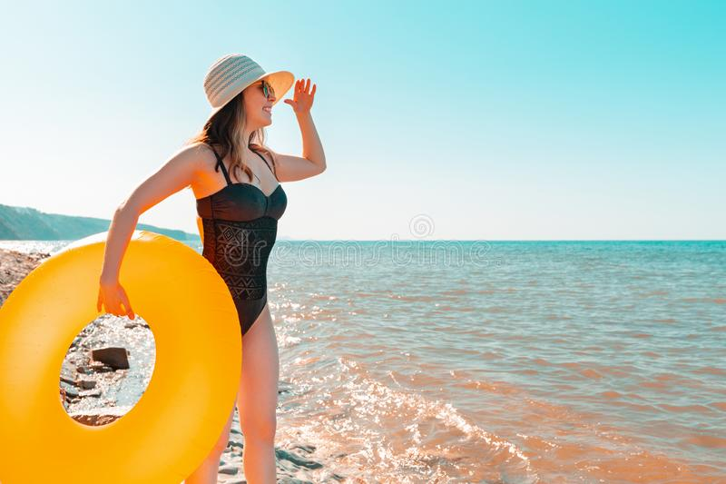 Молодая женщина в черном купальнике и шляпе, держащей оранжевый круг купания и смотря на расстояние Море в море стоковые фотографии rf