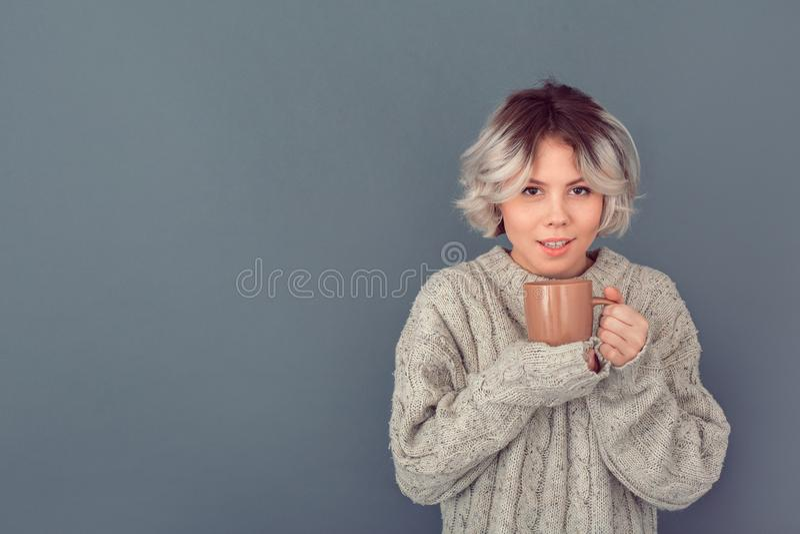 Молодая женщина в шерстяном свитере изолированном на молоке серой концепции зимы стены горячем стоковое изображение