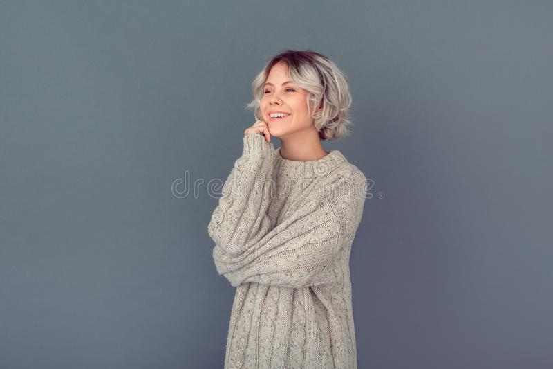 Молодая женщина в шерстяном свитере изолированном на серый мечтать концепции зимы стены стоковые фотографии rf