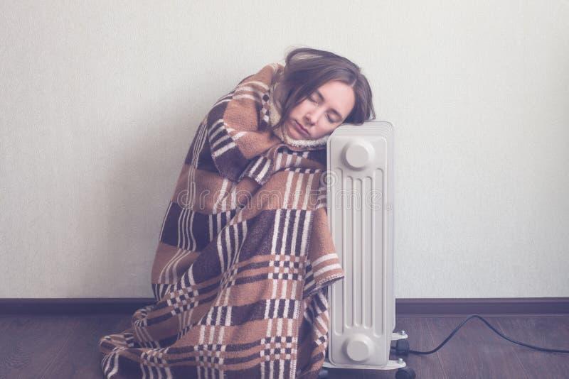 Молодая женщина в шерстяных руках подогрева шотландки над электронагревателем стоковые фотографии rf