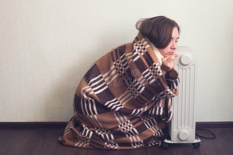 Молодая женщина в шерстяных руках подогрева шотландки над электронагревателем стоковое изображение