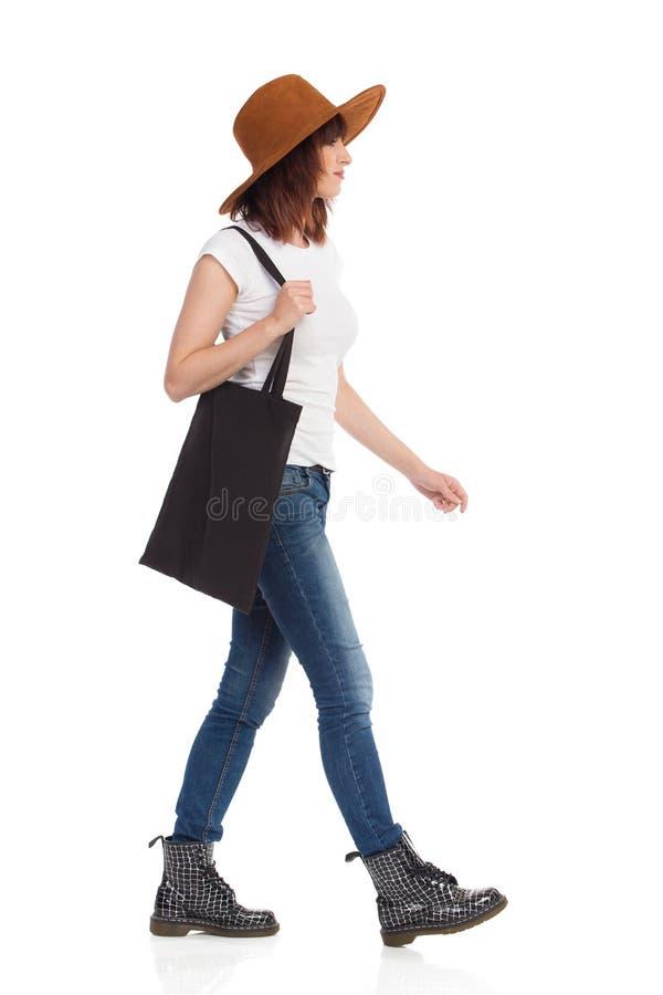 Молодая женщина в шляпе Брайна идет с черной сумкой на ее плече стоковое изображение
