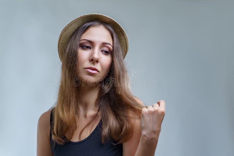 Молодая женщина в шляпе и черной рубашке гордо представлять изолированных на серой предпосылке в конце студии вверх стоковое изображение rf