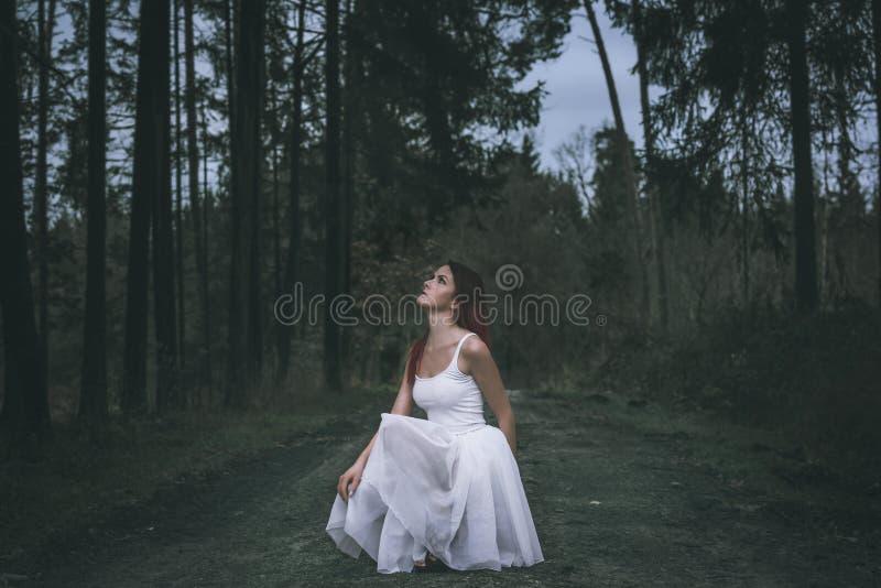 Молодая женщина в юбке балетной пачки смотря вверх стоковые фото