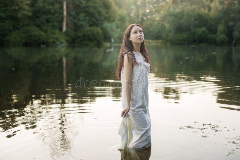 Молодая женщина в nightie стоит в реке стоковое изображение