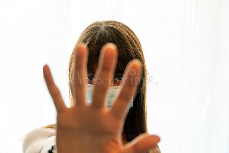 Молодая женщина, глядя сквозь пальцы, сигнализирует о том, чтобы остановиться рукой в маске лица стоковые изображения rf