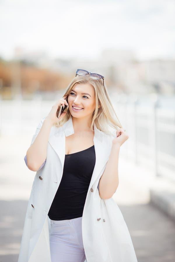 Молодая женщина говоря на ее мобильном телефоне слушая к переговору, она стоит outdoors на обваловке гранита против реки стоковое фото rf