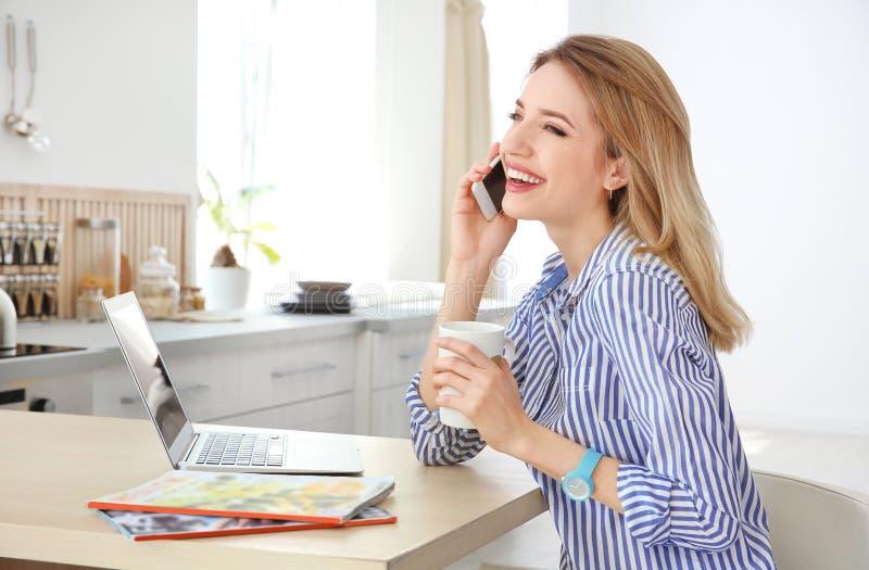 Молодая женщина говоря на телефоне пока использующ компьтер-книжку стоковое фото rf