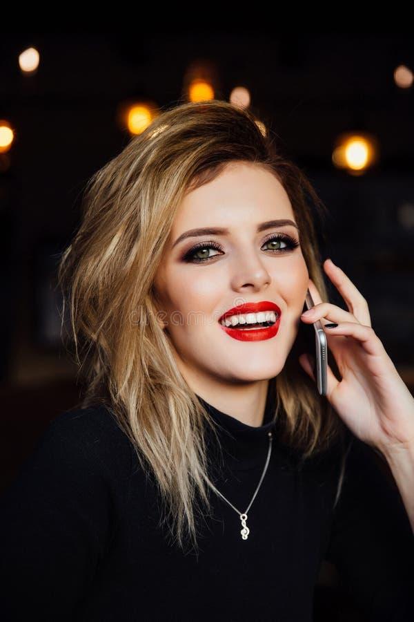 Молодая женщина говоря на телефоне с на таблицей в кафе стоковое изображение