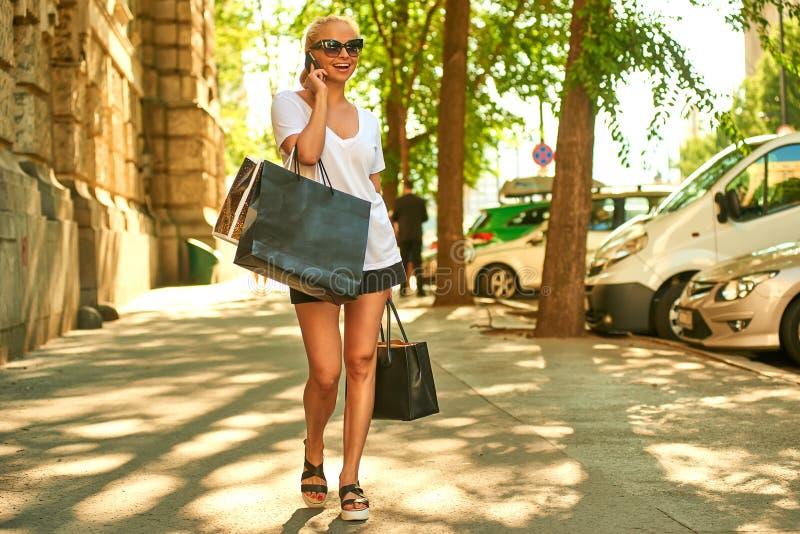 Молодая женщина говоря на телефоне на улице с сумками стоковое фото rf