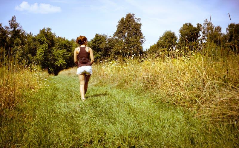 Молодая женщина гуляя прочь в природу стоковая фотография rf
