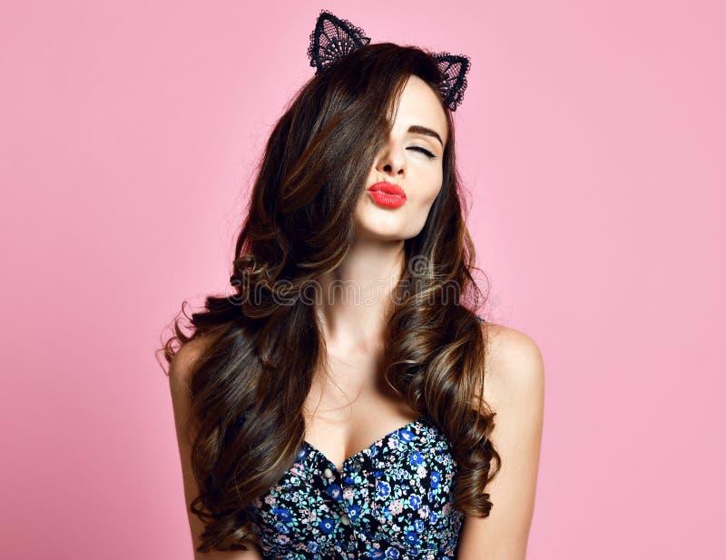 Молодая женщина дает поцелуй показывает что красные губы с составляют носят ретро девушку pinup предпосылки ушей кота стиля совре стоковые изображения
