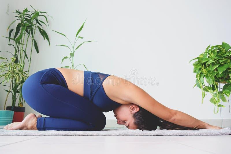 Молодая женщина делая йогу дома стоковые изображения