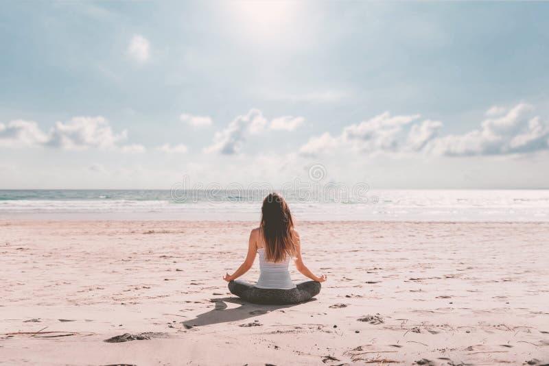 Молодая женщина делая йогу на пляже стоковые изображения