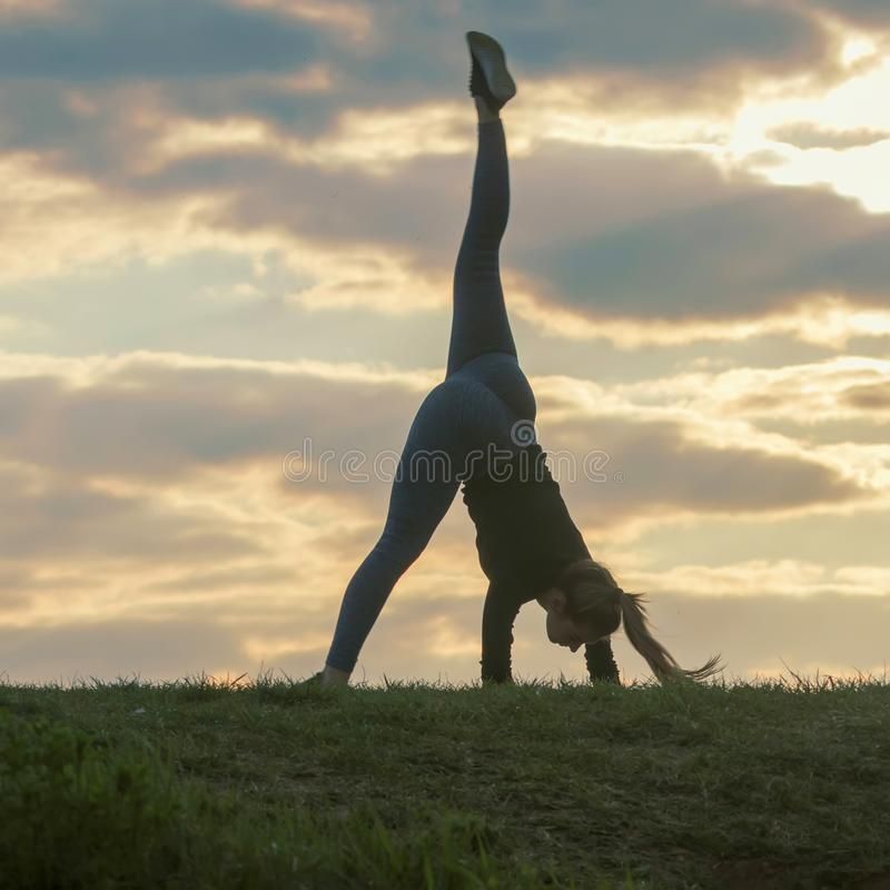 Молодая женщина делая колесо телеги на восходе солнца разминки утра травы красивом стоковые фото