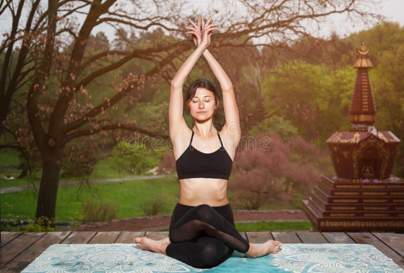 Молодая женщина делая тренировки йоги outdoors Раздумье йоги в парке стоковое фото