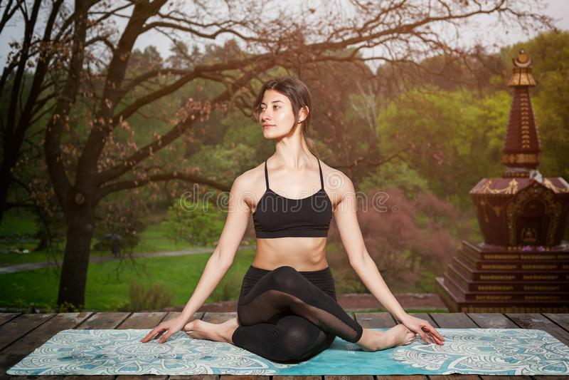 Молодая женщина делая тренировки йоги outdoors Раздумье йоги в парке стоковая фотография