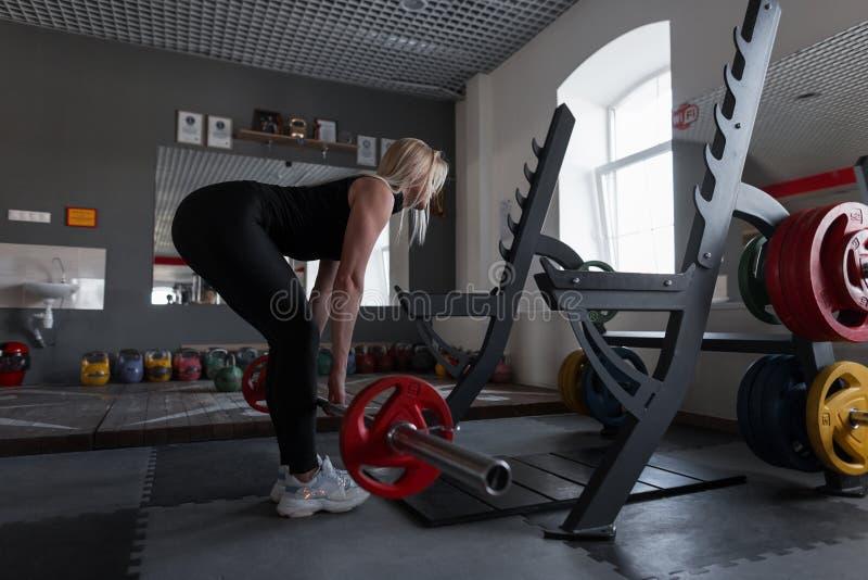 Молодая женщина делая тяжелую тренировку на спортзале со штангой Девушка в большей форме делая сидения на корточках в студии фитн стоковая фотография rf