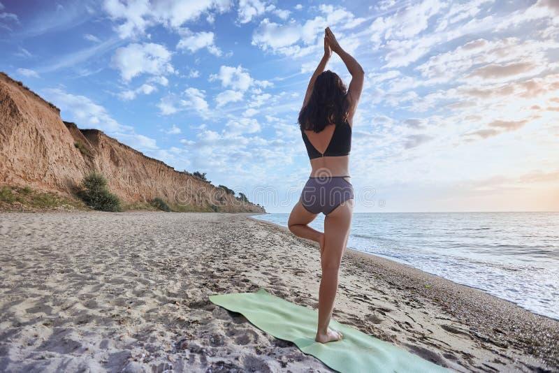 Молодая женщина делая asana йоги в природе с видом на океан Outdoors разминки утра, спорт и здоровый образ жизни стоковые фото