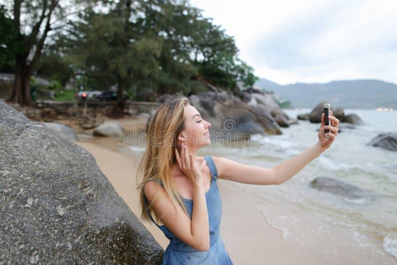 Молодая женщина делая selfie smartphone на пустом пляже около моря стоковые изображения rf