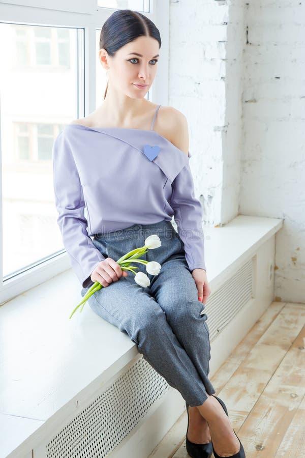 Молодая женщина дела в случайных одеждах с букетом тюльпанов в его руках стоковое изображение rf