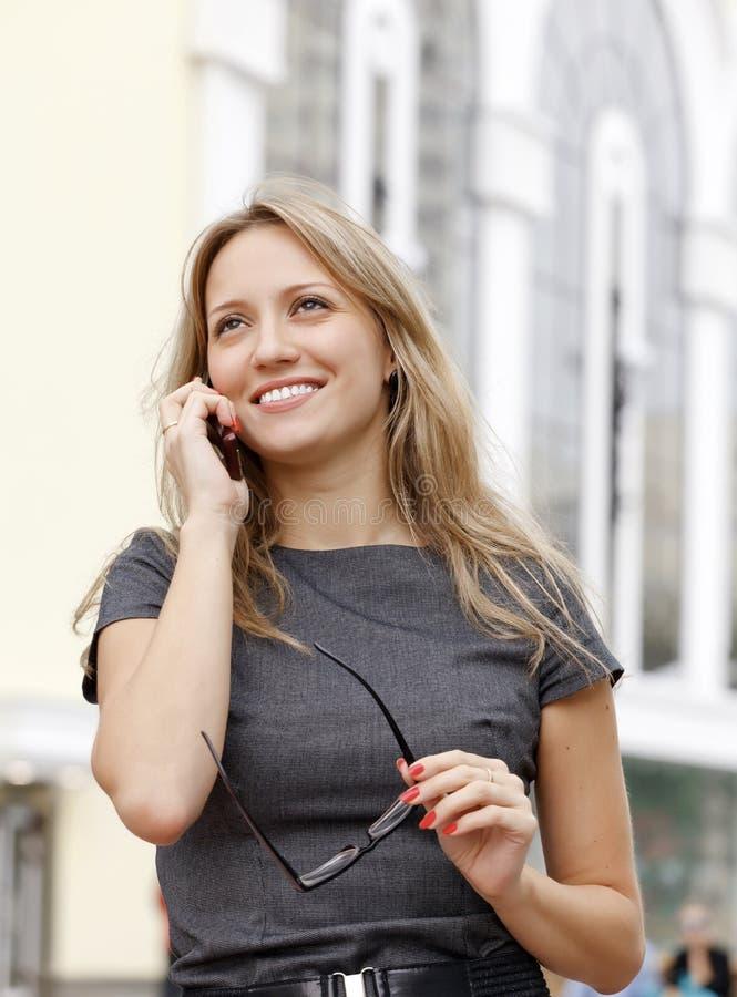 Молодая женщина дела говоря телефоном стоковая фотография