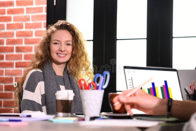 Молодая женщина дела сидя на столе в офисе стоковые изображения rf