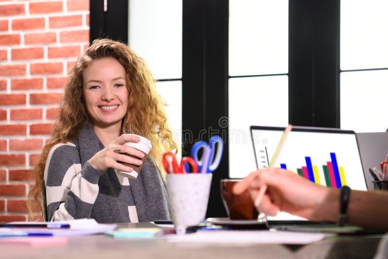 Молодая женщина дела сидя на столе в офисе стоковые фотографии rf