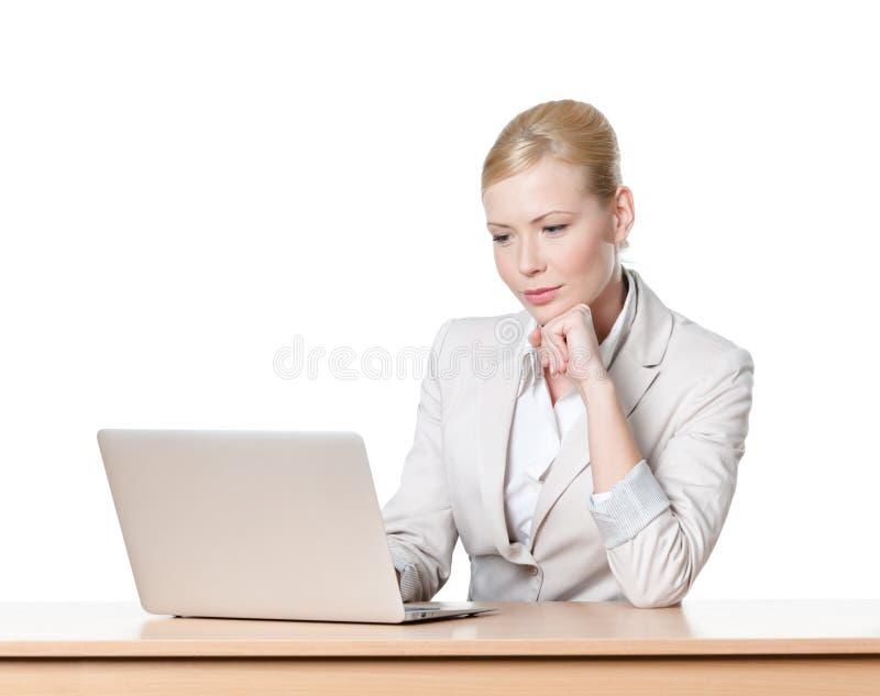 Молодая женщина дела сидя на столе с компьтер-книжкой стоковая фотография