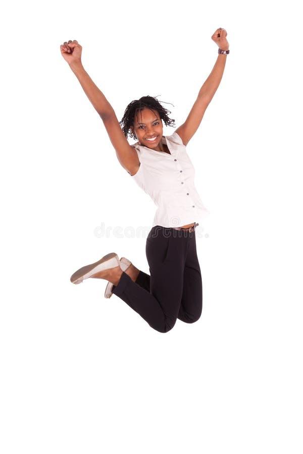 Молодая женщина дела скача, принципиальная схема афроамериканца успеха стоковая фотография