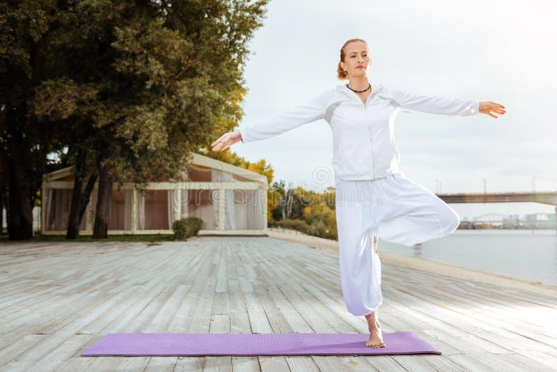 Молодая женщина держа баланс пока делающ тренировки стоковое фото rf