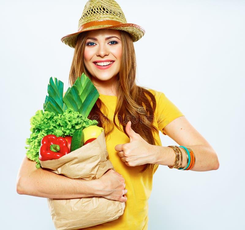 Молодая женщина держа бумажную сумку с вегетарианской едой стоковые фотографии rf