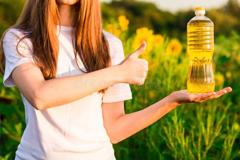 Молодая женщина держа бутылку масла в больших пальцах руки поля и выставки солнцецвета вверх стоковое фото rf
