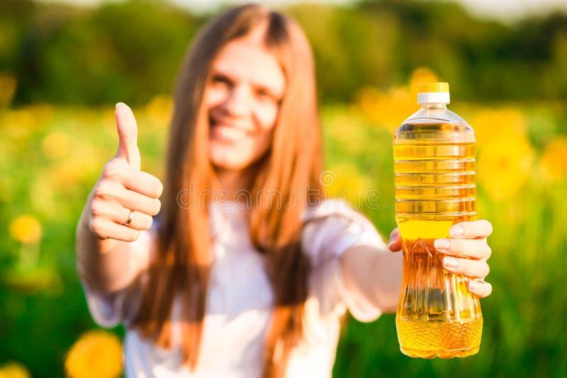 Молодая женщина держа бутылку масла в больших пальцах руки поля и выставки солнцецвета вверх стоковое изображение