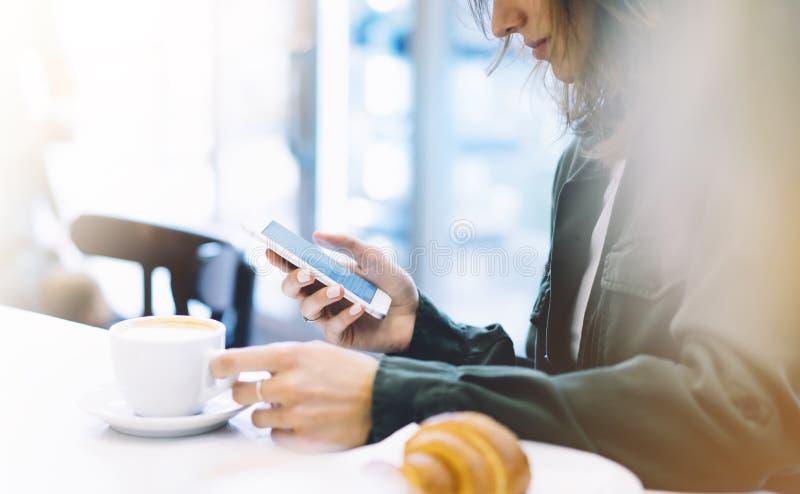 Молодая женщина держа в женщине вручает мобильный телефон и питье горячие кофе ароматности или чай во времени завтрака, девушка п стоковое изображение rf