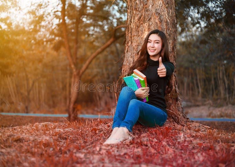 Молодая женщина держа книгу и показывая большой палец руки вверх подписывает внутри парк стоковое изображение