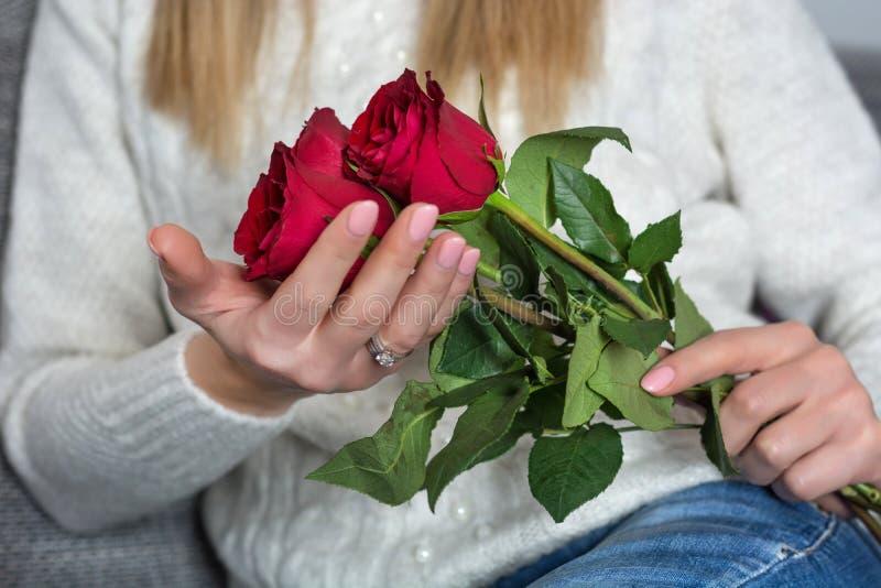 Молодая женщина держа красивую красную розу в руках и сидя в кровати дома стоковое изображение rf