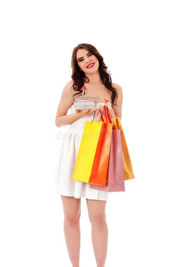 Молодая женщина держа малые пустые корзину для товаров и хозяйственные сумки стоковые фото