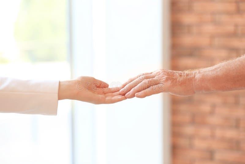Молодая женщина держа пожилую руку человека внутри помещения стоковое фото rf