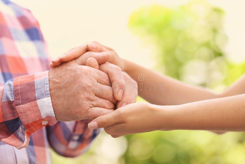 Молодая женщина держа пожилые руки человека стоковое фото