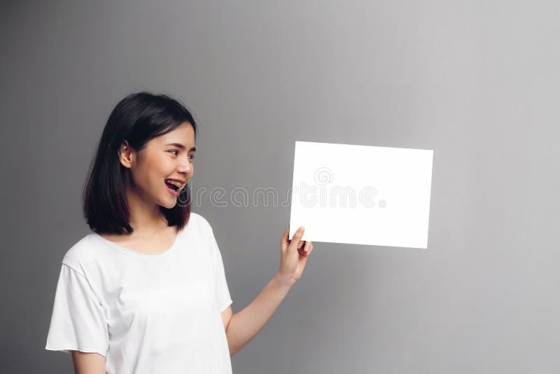 Молодая женщина держа пустой плакат для текста на белой предпосылке стоковые фото