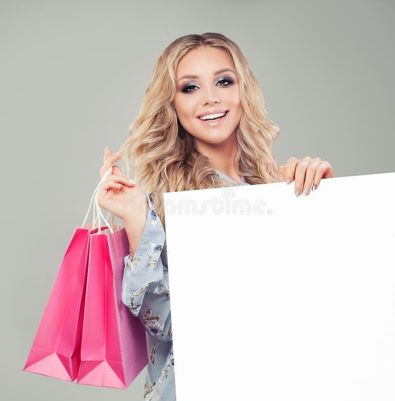 Молодая женщина держа розовые хозяйственные сумки и белая пустая доска стоковые фото