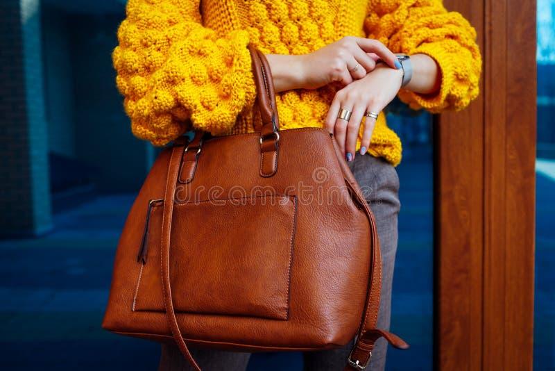 Молодая женщина держа стильную сумку и нося желтый свитер Одежды и аксессуары весны женские m стоковое фото