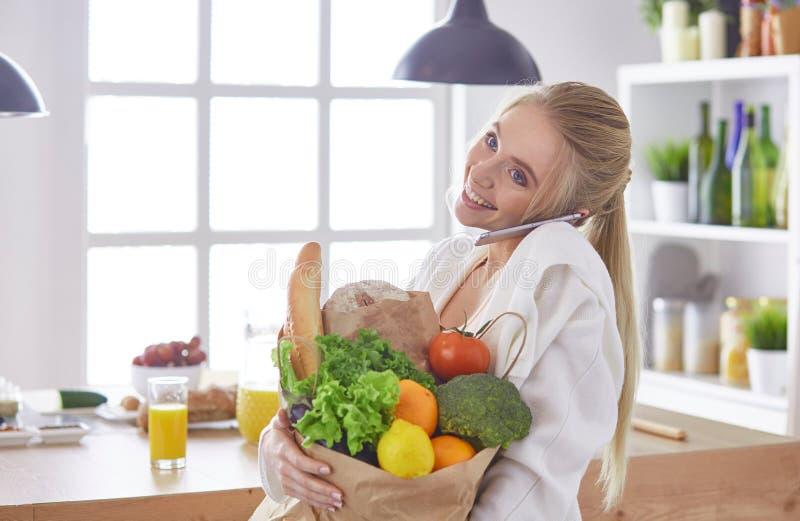 Молодая женщина держа сумку посещения магазина бакалеи с овощами стоя в кухне стоковое фото