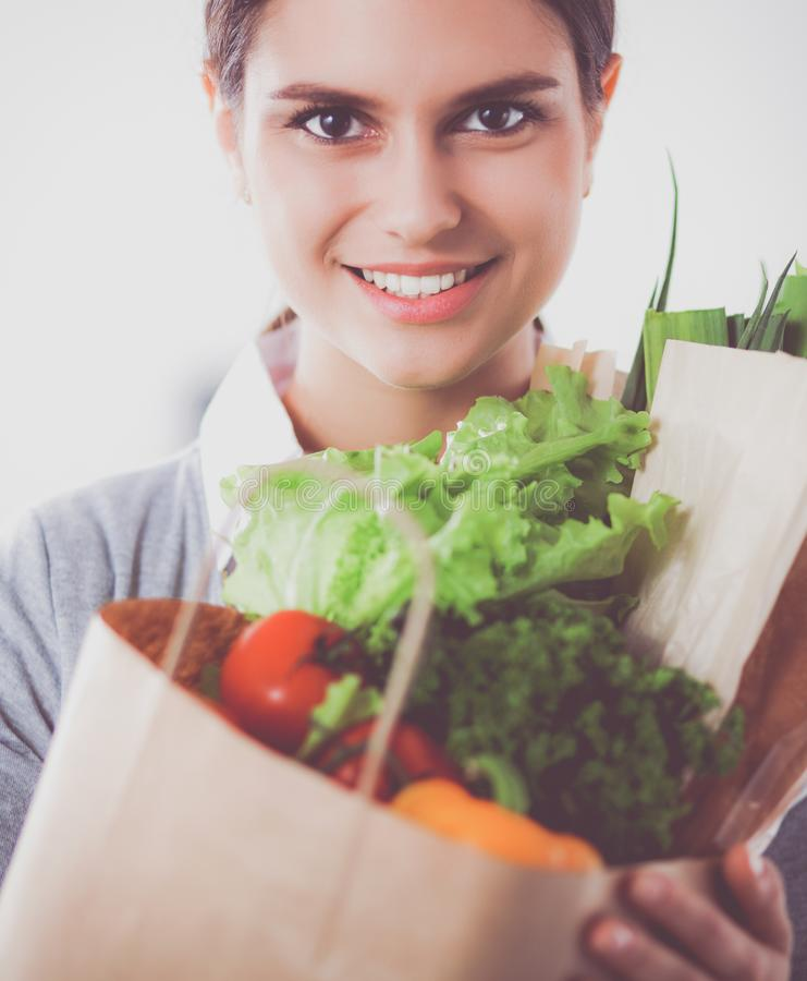 Молодая женщина держа сумку посещения магазина бакалеи с овощами Стоять в кухне стоковое фото