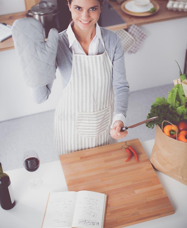 Молодая женщина держа сумку посещения магазина бакалеи с овощами Стоять в кухне стоковое изображение