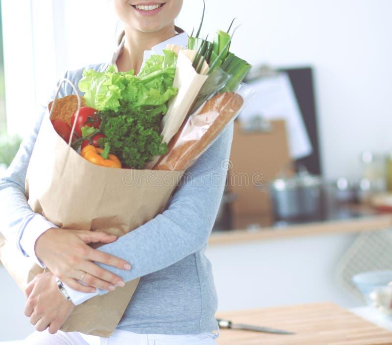 Молодая женщина держа сумку посещения магазина бакалеи с овощами Стоять в кухне стоковая фотография rf